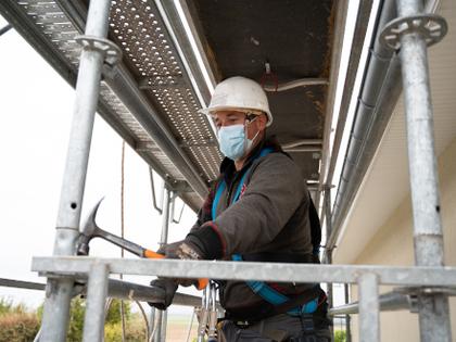 Un opérateur sur un échafaudage portant un masque respiratoire
